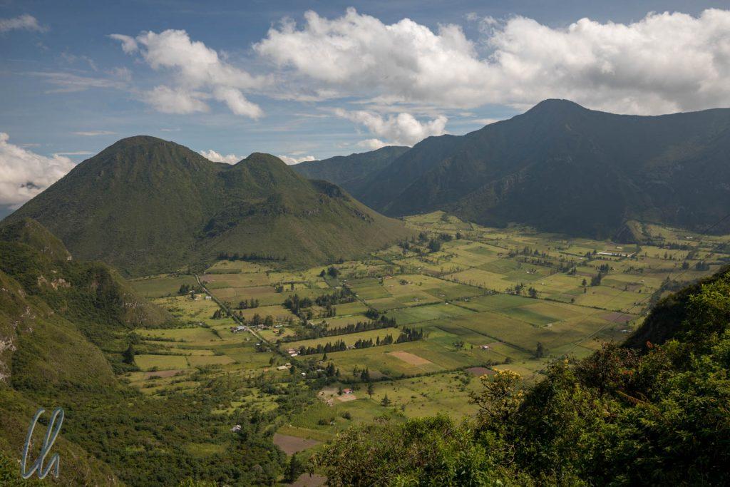 """Blick in den Pululahua Krater von """"El Mirador"""". Der Berg links im Hintergrund gehört nicht zum Kraterrand. Er ist ein ein Hügel im Krater."""