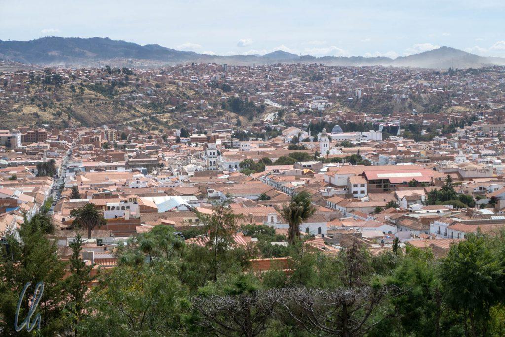 In Sucre wächst viel Grün zwischen den roten Dächern.
