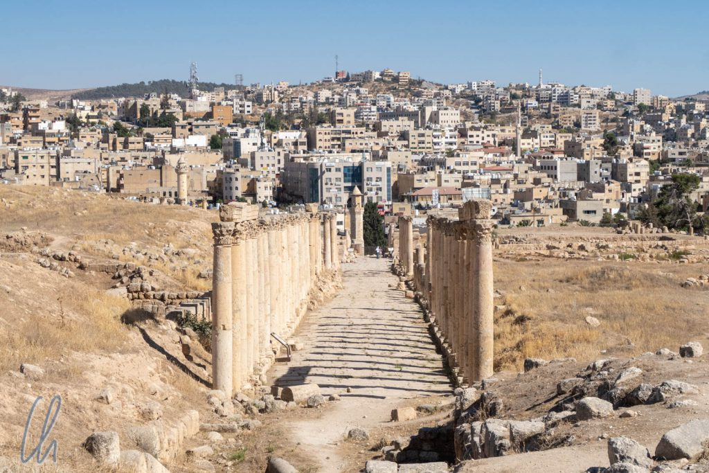 Blick über den historischen Decumanus zum modernen Jerash.