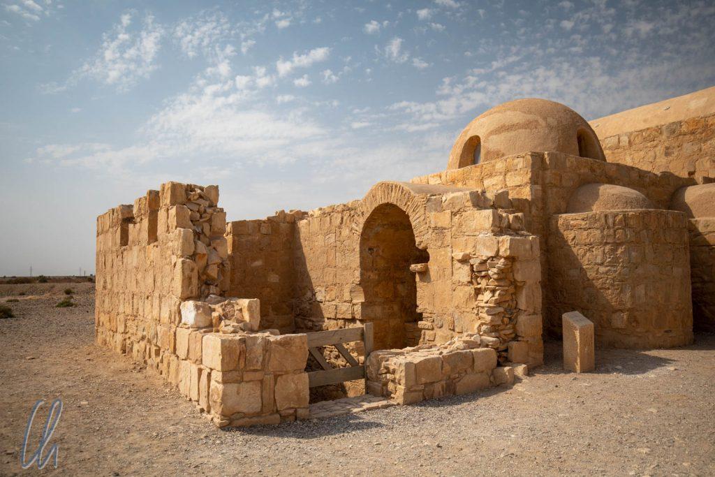 Von außen eher unscheinbar und Ton in Ton mit der umgebenden Wüste: Qusair 'Amra