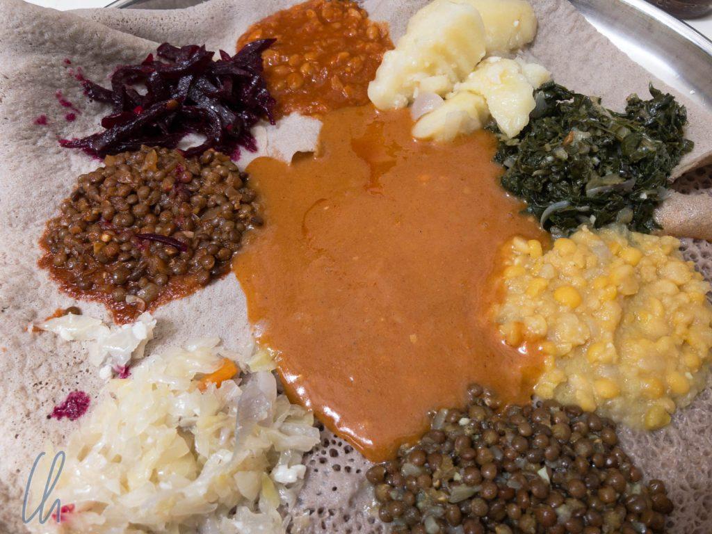 Injera mit zahlreichen Beilagen (Beyaynetu): Mehrere Personen essen von einer Platte.