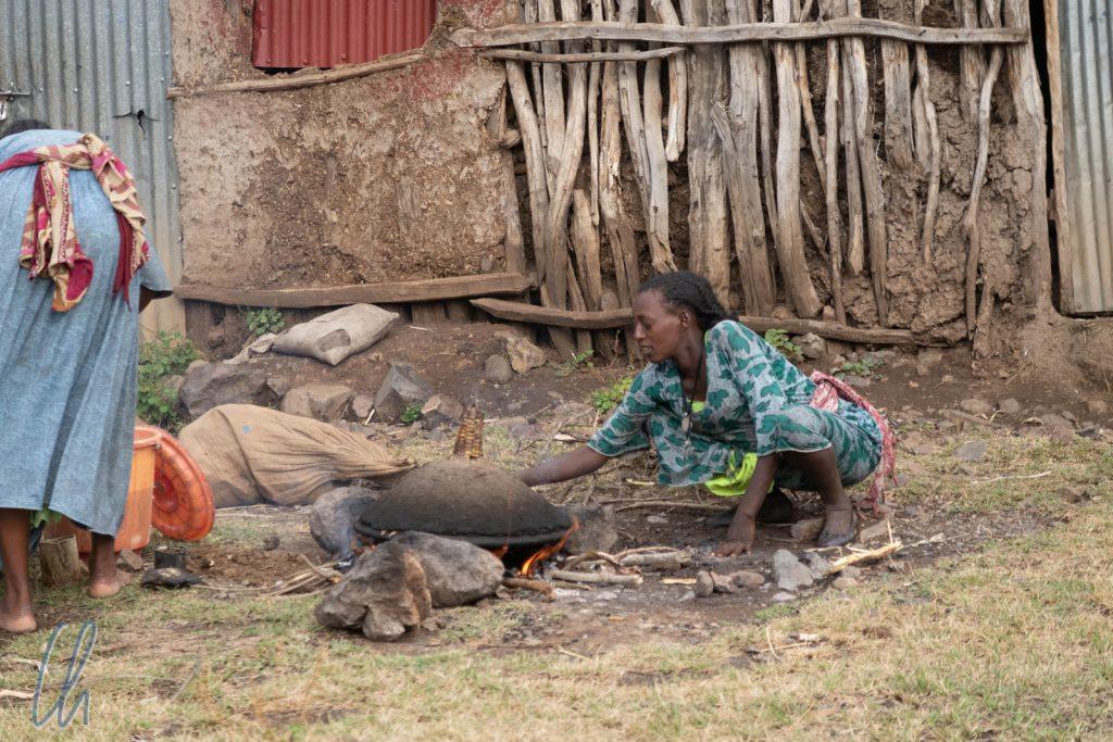 Eine Frau backt Injera vor ihrem Haus.