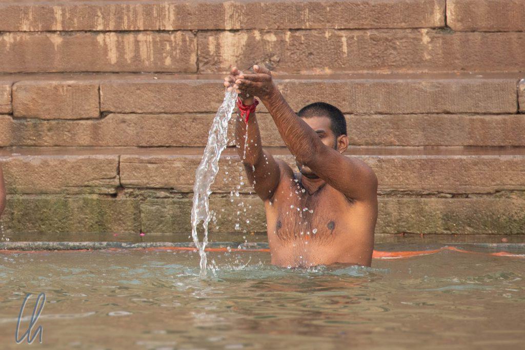 Der Betende ließ das Heilige Wasser rituell aus den Händen rinnen.