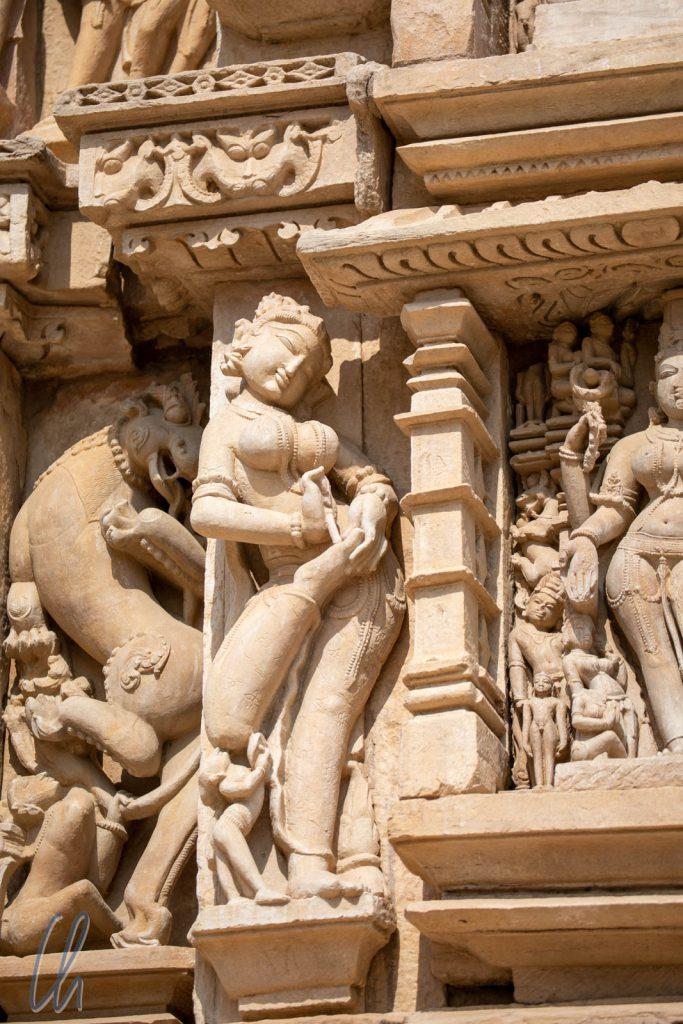 Eine Surasundari entfernt sich einen Dorn aus ihrem Fuß am Parshvanath Tempel.