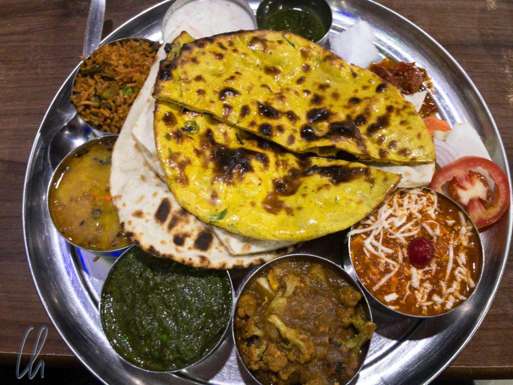 Ein vegetarisches Thali mit Dal, einem Blumenkohl-Curry, Palak Paneer, Reis, Raita und Naan