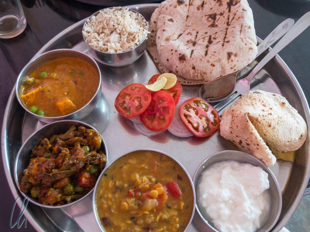 Ein vegetarisches Thali mit Mattar Paneer, einem Okra-Gericht, Dal, Reis, Chapati, Papadam und Joghurt
